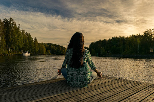 Woman on a dock sitting cross legged and meditating